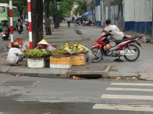 Photo of a lady eating soup and selling vegetables beside a man relaxing on a motorcycle on a footpath in Ho Chi Minh