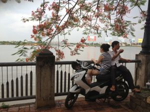 A couple eating their lunch on a motorcycle by the river.