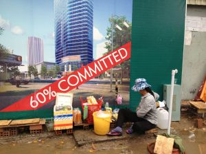 A vendor selling drinks from a bucket, sitting on a board, surrounded by a puddle of mud, with a sign advertising a new highrise development behind her.