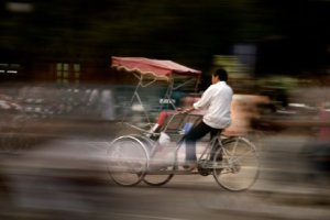 photo of a cyclo rider on a blurred and busy street