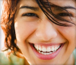 Photo of a girl smiling broadly.