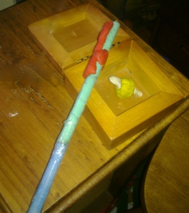 Photo of a handmade wand with a golden snitch in a box.